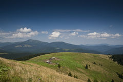 Shielings on a subalpine meadow on a slope of a mountain in the Carpathian mountains Royalty Free Stock Photos