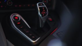 Shift knob of automatic gearbox in car interior. Modern car interior, view of the car`s gearbox knob stock video footage