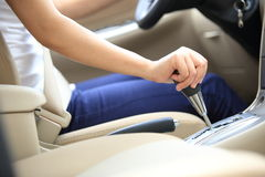 Shifting car gear stick. Woman driving a car and shifting the gear stick Stock Photo