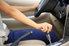 Shifting car gear stick. Woman driving a car and shifting the gear stick Stock Image
