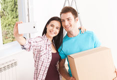 Shifting to a new life. Portrait of happy couple in new home. Portrait of happy couple in new home. Young couple holding box and smiling happily at phone camera Stock Photo