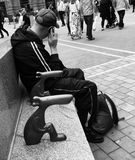 Shifty looking man on mobile telephone. Rough looking man wearing tracksuit and baseball cap talking on his mobile phone whilst sitting on a bench in city centre stock images
