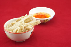 Shiitake mushroom snack in cup. With chilli sauce placed on a red background Royalty Free Stock Photos