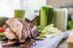 Shiitakechampinjoner och andra grönsaker som huggas av och skivas för ett strikt vegetariansushimål arkivbilder