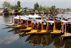 Shikara fartyg på Dal Lake med husbåtar Fotografering för Bildbyråer