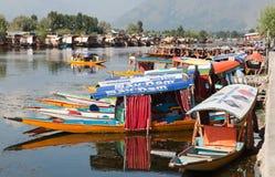 Shikara fartyg på Dal Lake med husbåtar Arkivfoto