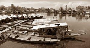 Shikara fartyg på Dal Lake med husbåtar Royaltyfri Foto