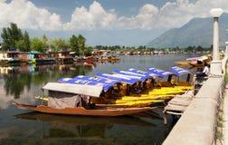 Shikara fartyg på Dal Lake med husbåtar Arkivfoton