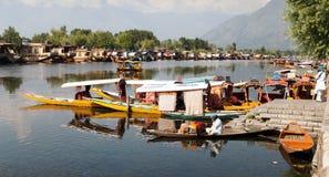 Shikara fartyg på Dal Lake med husbåtar i Srinagar Arkivfoto