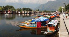 Shikara fartyg på Dal Lake med husbåtar i Srinagar Royaltyfri Fotografi