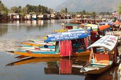 Shikara fartyg på Dal Lake med husbåtar i Srinagar Royaltyfria Bilder