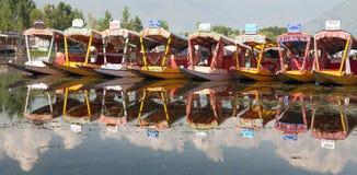 Shikara fartyg på Dal Lake med husbåtar i Srinagar Royaltyfri Foto