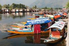 Shikara fartyg på Dal Lake med husbåtar i Srinagar - Shikara är ett litet fartyg som in används för trans. Arkivbild