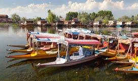 Shikara fartyg på Dal Lake med husbåtar i Srinagar Royaltyfria Foton