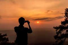 Shilouette of man taking a photo of sunset with smartphone Royalty Free Stock Image