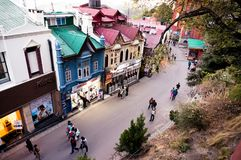 Branded showrooms on the Mall street in Shimla. Shimla, India - 25th Apr 2018: Branded showrooms with lights on the mall road in Shimla housed in british styled Royalty Free Stock Image