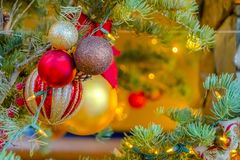 Shimmering baubles and lights on a Christmas Tree. Cluster of shiny and shimmering baubles hanging on a holiday tree. The Christmas tree is illuminated by a stock photography
