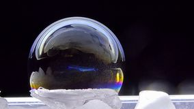 Shimmering colors of soap bubbles on ice.