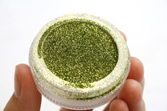 Shimmering glitter. Shimmering green glitter held by a white caucasian female isolated with a white background Stock Photos