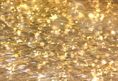 Shimmering Gold Water Bokeh Background. Beautiful bokeh lights in shimmering gold water royalty free stock photo