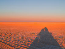 Shimmering horizon and long shadows as sun sets across Makgadikgadi Pans National Park, scenic large flat area of salt pan desert. Of Botswana royalty free stock photography