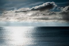 Shimmering Light on Sea with Moody Dark Sky Stock Image