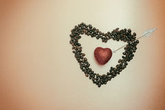 Shimmering red heart inside symbolic heart of coffee beans. Pier Royalty Free Stock Image