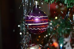 Old fashioned round glass Christmas tree ornament. Shimmering red, white, and purple old-fashioned round glass Christmas tree ball ornament reflecting red and Royalty Free Stock Photography