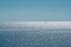 Shimmering sea. A lone sailboat on a shimmering sea stock photos