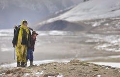 Shimshali dama i jej syn wspinamy się w niebezpiecznych tereny przynosić do domu przegranych yaks zdjęcie stock