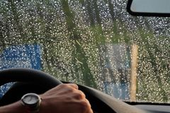 Shine Raindrops on the windshield. Нand of a man in a watch. Shine Raindrops on the windshield  Hand man watch helm rain sun drop car Royalty Free Stock Photo