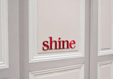 Shine!!. A red message saying Shine on a white wooden background Stock Photo