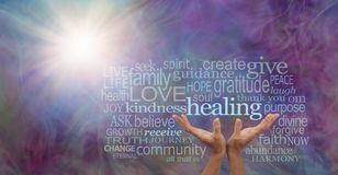 Shine your healing light word cloud. Female hands reaching up to the word HEALING surrounded by a relevant word cloud with a sun burst and wispy multi coloured Royalty Free Stock Image