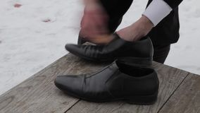 Shines shoes on the porch of an old building stock footage