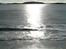 Shiney Wave. Sun reflects off of this wave on a sandy beach Stock Image