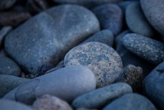 A shingle beach or beach stone. A shingle beach also referred to as rocky beach or pebble beach is a beach which is armoured with pebbles or small- to medium stock photography
