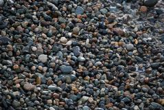 A shingle beach or beach stone. Shingle beaches are typically steep, because the waves easily flow through the coarse, porous surface of the beach, decreasing stock images