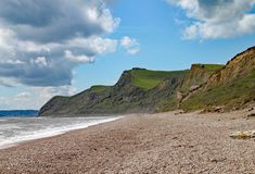 The shingle beach at Eype in Dorset on a sunny day, The sandstone cliffs of the Jurassic coast can be seen in the background stock images