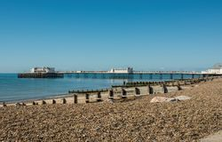 Beach and pier at Worthing, Sussex, England. Shingle beach and pier on the seafront at Worthing, West Sussex, England Royalty Free Stock Photos
