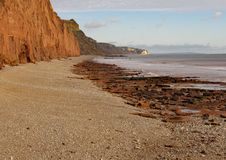 The shingle beach at Sidmouth in Devon with the red sandstone cliffs of the Jurassic coast in the background royalty free stock photo