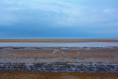 Shingle rocky beach of Norfolk coast and  dark blue sky, Northern Sea, Holkham beach, United Kingdom Stock Image