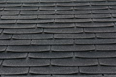 Shingles on a Roof. A picture of a roof with black, curved shingles stock image