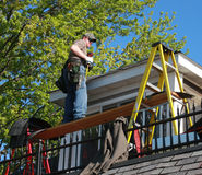 Shingling house roof. Carpenter shingling a roof on a house remodel Stock Images