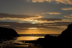 Shining through. Sunset, Little Haven, Pembrokeshire, Wales - sunset and warm coloured clouds Royalty Free Stock Photo