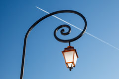 Shining Backlit Streetlamp and Airplane Trail Stock Images