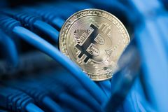 Shining bitcoin simbol in blue cables closeup. Cryptocurrency, d Stock Images