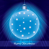 Shining blue glossy christmas ball. On dark background with rays of light Stock Photos