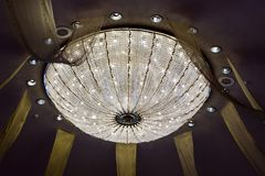 Shining chandelier hanging on a ceiling in hotel Royalty Free Stock Photo
