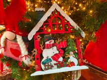 Shining Christmas tree with little wooden house with snowman family Royalty Free Stock Photo