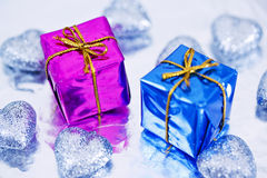 Shining colorful Christmas presents. Blue and purple Christmas gift and heart decorations royalty free stock photography